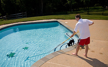 man cleaning his pool